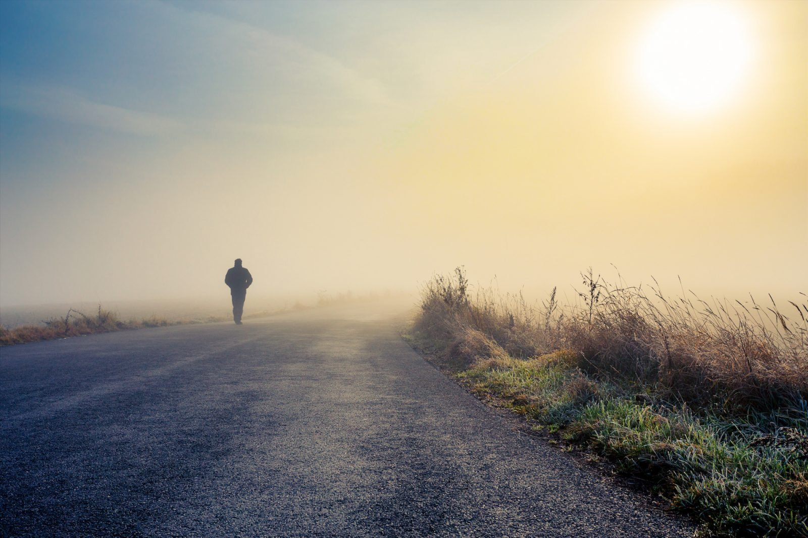 A person walk into the misty foggy road in a dramatic mystic sunrise scene with abstract colors