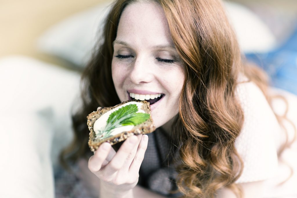 Chica practica oligoterapia comiendo una tostada saludable