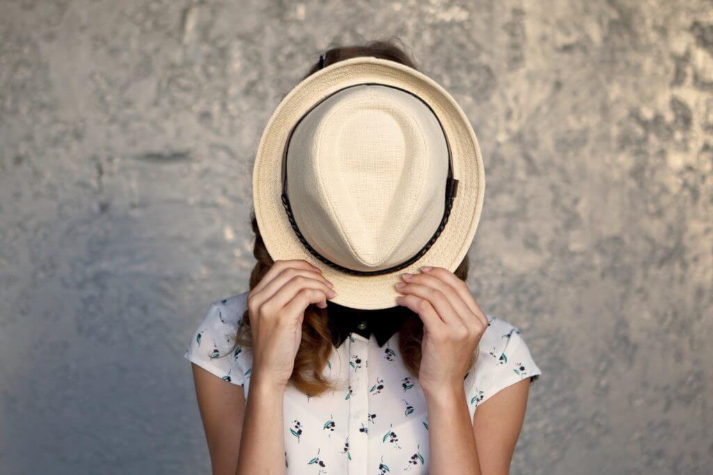 Chica oculta su cara con un sombrero porque siente un sentimiento de culpa